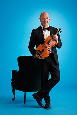 Daniel Scholz holding his viola in front of a chair