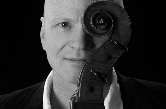 Philip Hansen headshot with scroll of his cello covering his left eye